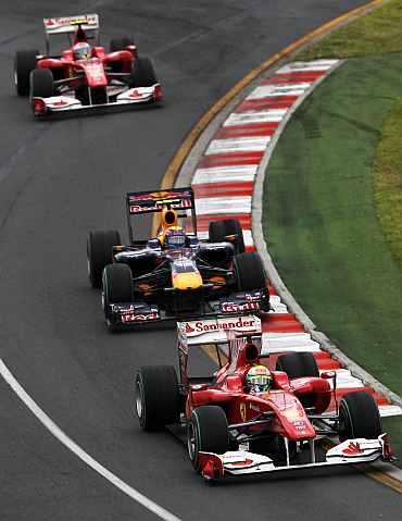 A Ferrari car races ahead of the Red Bull car