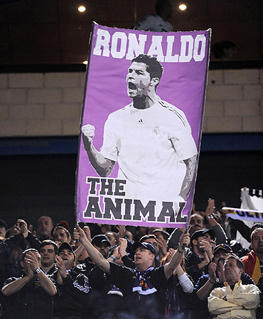 A Real Madrid fan holds up a banner of Cristiano Ronaldo before the start of the match between Atletico Madrid on Saturday