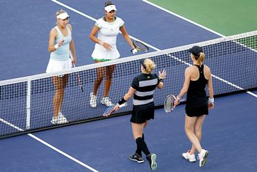 Sania and Elena are congratulated at the net by Bethanie Mattek-Sands and Meghann Shaughnessy