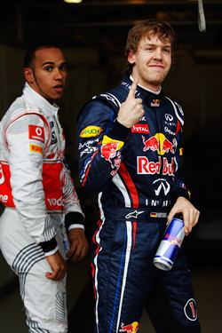 Vettel celebrates after taking pole in Melbourne. In the background is Hamilton