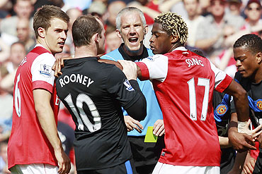 Manchester United's Wayne Rooney and Arsenal's Alex Song get physical