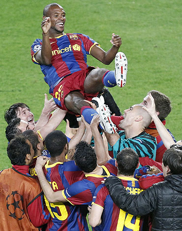 Barcelona's Eric Abidal (top) is lifted by teammates as they celebrate victory over Real Madrid