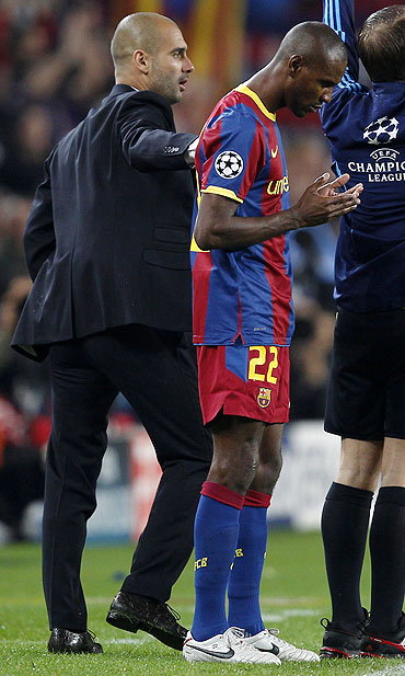 Eric Abidal says a prayer as Pep Guardiola pats him on the back before entering the pitch