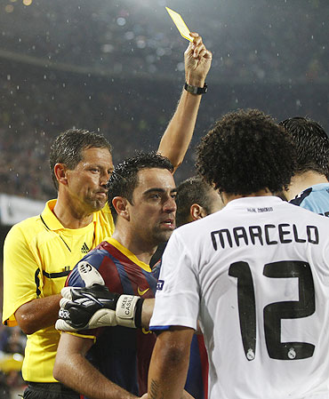 Referee Frank de Bleeckere shows the yellow card to Real Madrid's Marcelo (right) even as he argues with Barcelona's Xavi (centre)