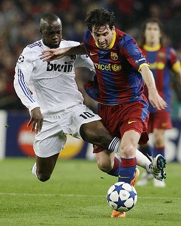 Real Madrid's Lassana Diarra (left) battles for possession with Barcelona's Lionel Messi