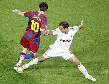 Real Madrid's Ricardo Carvalho fouls Barcelona's Lionel Messi (left)