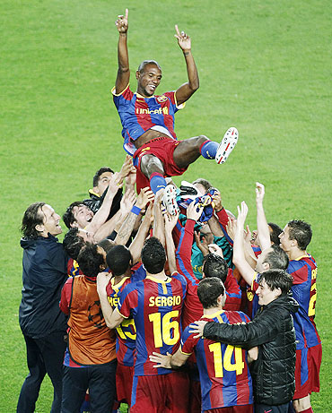 Barcelona's players celebrate with team-mate Eric Abidal (top)