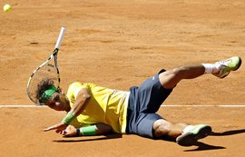 Nadal falls down during his match against Paolo Lorenzi