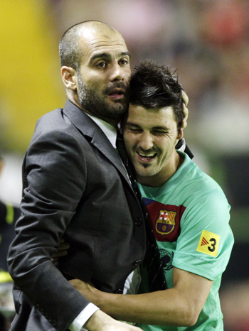 Barcelona's coach Pep Guardiola (L) embraces David Villa after winning the Spanish league in Valencia