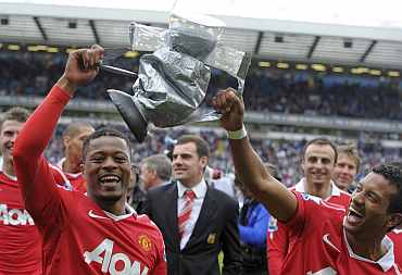 Nani and Patrice Evra with the dummy trophy after winning against Blackburn