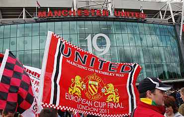 Manchester United supporters wave flags outside the stadium before their English Premier League match