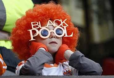 A young Blackpool supporter watches from the stand during their English Premier League soccer match