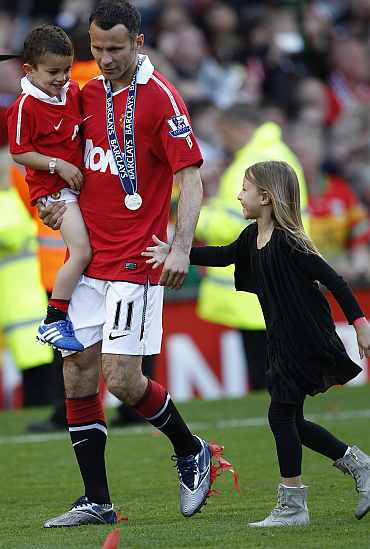 Manchester United's Giggs holds his children Zach and Libby
