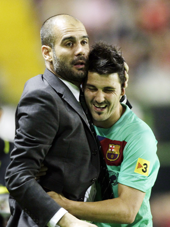 Barcelona's coach Pep Guardiola (L) embraces David Villa after winning the Spanish first division soccer league