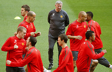 Manchester United manager Alex Ferguson (centre) watches his players go through the grind during a training session at Wembley Stadium in London on Friday