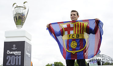 A Barcelona fan poses for a photograph next to the Champions League trophy on display at the UEFA Champions Festival in Hyde Park in London on Friday