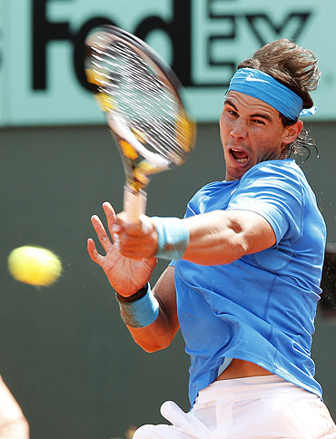 Rafael Nadal of Spain returns the ball to Antonio Veic of Croatia