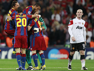 Manchester United's Wayne Rooney (right) walks past as Barcelona's players celebrate their Champions League final victory