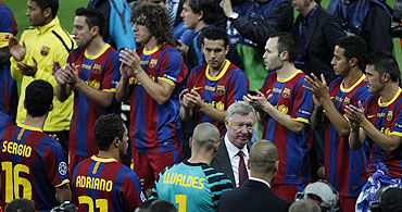 Barcelona's players applaud as Manchester United's manager Alex Ferguson walks by after their Champions League final