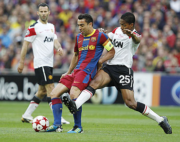Manchester United's Antonio Valencia (right) and Barcelona's Xavi vie for possession