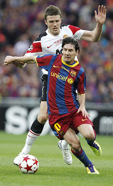Manchester United's Michael Carrick (rear) challenges Barcelona's Lionel Messi