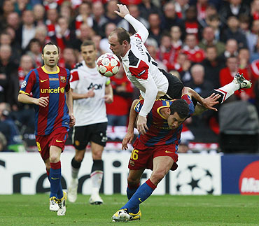 Manchester United's Wayne Rooney (top) jumps over Barcelona's Sergio Busquets as Andres Iniesta (left) looks on