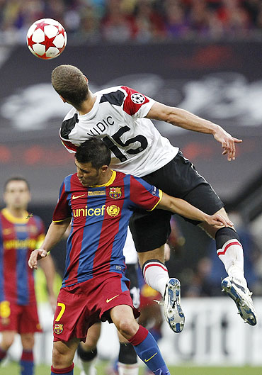 Manchester United's Nemanja Vidic (top) jumps for the ball over Barcelona's David Villa