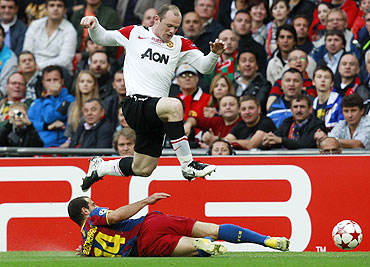 Manchester United's Wayne Rooney (top) trips over Barcelona's Javier Mascherano