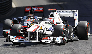 Sauber's driver Kamui Kobayashi (right) drives past McLaren's Lewis Hamilton