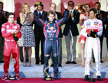 Red Bull's Sebastian Vettel (centre) celebrates on the podium with Ferarri's Fernando Alonso and McLaren's Jenson Button
