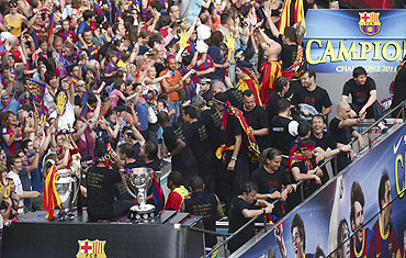Barcelona's players celebrate atop a bus with their supporters on the streets of Barcelona on Sunday