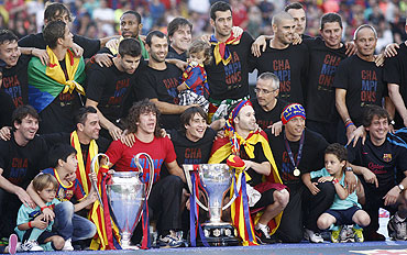 Barcelona's team pose with the Champions League and La Liga trophies after winning their Champions League final against Manchester United