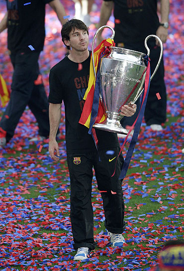 Barcelona's Lionel Messi holds the Champions League trophy at Camp Nou stadium in Barcelona