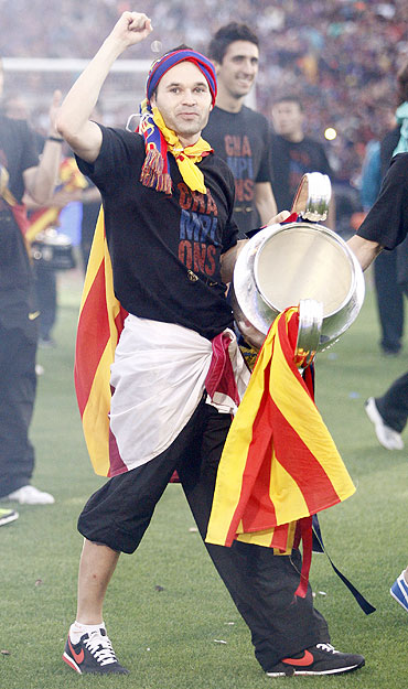 Barcelona's player Andres Iniesta holds the Champions League trophy at Camp Nou stadium in Barcelona on Sunday