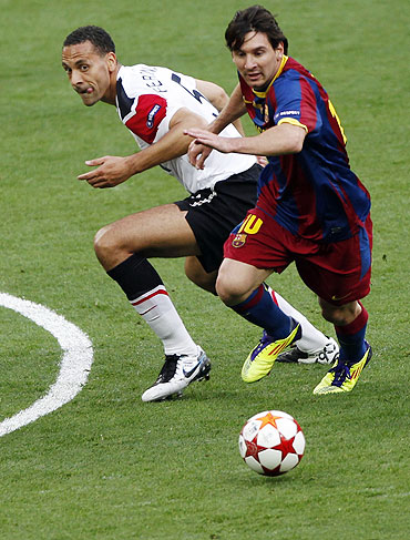 Manchester United's Rio Ferdinand (left) and Barcelona's Lionel Messi vie for possession