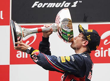 Red Bull's Sebastian Vettel drinks champagne from the trophy after winning the Indian GP
