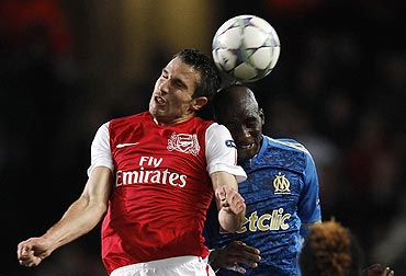 Arsenal's Robin van Persie and Marseille's Rod Fanni challenge for the ball