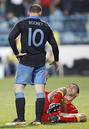 Montenegro's Miodrag Dzudovic (right) reacts after a challenge by England's Wayne Rooney who was sent off during their Euro 2012 qualifier