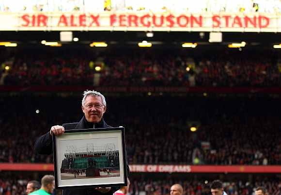 Sir Alex Ferguson is presented with a photo to commemerate his 25th year as manager, as the North Stand is renamed the 'Sir Alex Ferguson Stand'