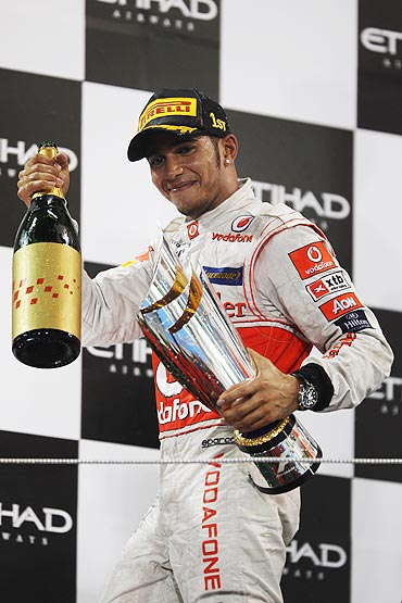 Lewis Hamilton of McLaren celebrates on the podium after winning the Abu Dhabi Formula One Grand Prix