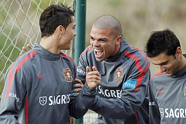 Portugal's Pepe (centre) accompanied by Helder Postiga (right) joke with Cristiano Ronaldo before their training session in Obidos