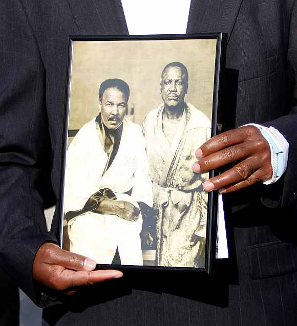 A mourner holds a photograph of boxing greats Muhammad Ali and Joe Frazier