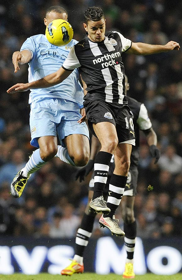 Manchester City's Vincent Kompany (left) challenges Newcastle United's Hatem Ben Arfa