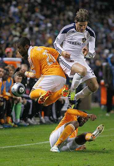 Corey Ashe of the Houston Dynamo collides with David Beckham of the Los Angeles Galaxy