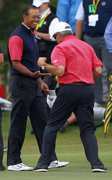 Tiger Woods of the US Team celebrates with U.S. Team captain Fred Couples after winning his match