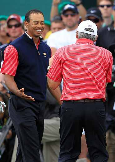 Tiger Woods of the U.S. Team celebrates with U.S. Team captain Fred Couples after winning his match