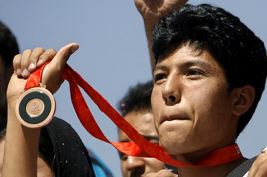Rohullah Nikpai holds up the bronze medal he won at the 2008 Olympic Games