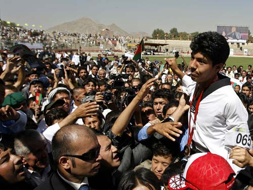 Rohullah Nikpai is carried by the crowd during a procession for his homecoming in Kabul from the Beijing 2008 Olympic Games