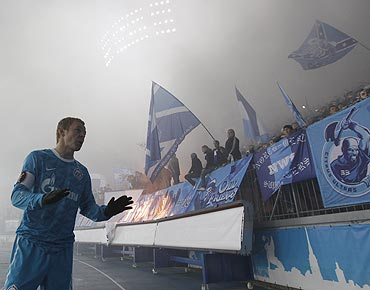 Zenit St. Petersburg's Aleksandr Anyukov attempts to calm down supporters who burn flares during the Champions League Group G soccer match against APOEL Nicosia at Petrovsky stadium in St. Petersburg