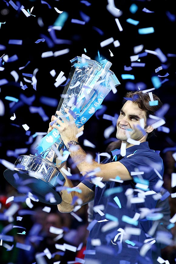 Roger Federer celebrates with the trophy after winning the World Tour finals on Sunday